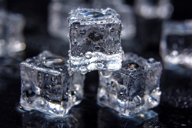 Alcuni cubetti di ghiaccio sul tavolo di vetro. isolato su sfondo nero cubetti di ghiaccio in fusione
