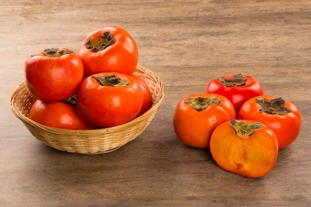 Alcuni frutti di cachi su una superficie di legno. frutta fresca.