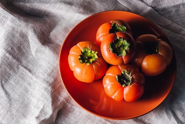 Alcuni cachi sul piatto arancio