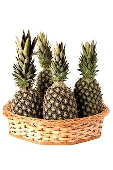 Alcuni ananas nel cesto di vimini su sfondo bianco isolato.
