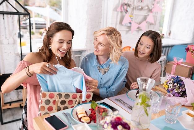 Alcuni regali. due amichevoli colleghi eccitati si sentono benissimo mentre fanno dei regali alla loro amica incinta