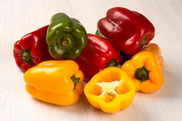 Alcuni peperoni rossi, verdi e gialli su una superficie di legno. verdura fresca.