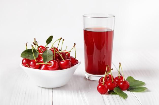 Alcune ciliegie mature vicino a un bicchiere di succo di ciliegia fresca e ciotola con ciliegie su tavole di legno bianche contro la parete chiara.