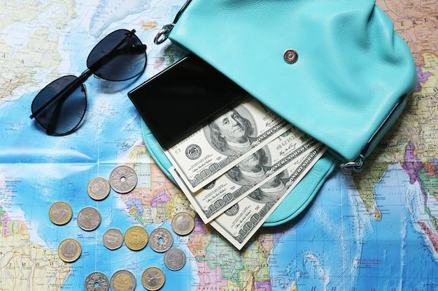 Alcuni membri del personale per i viaggi. soldi, occhiali, borsa, telefono, monete sulla mappa.