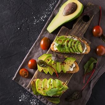 Alcuni tostati con avocado verde su cemento nero