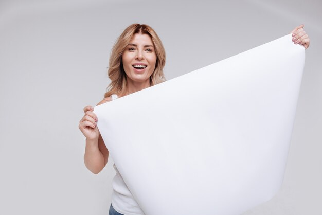 Alcune informazioni utili. incoraggiare la giovane donna radiosa che tiene un grande foglio di carta bianco mentre sta in piedi e sorride