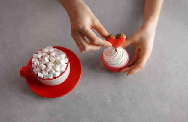 Un innamorato prepara cupcakes per una persona cara per san valentino, decorando il dolce con un cuore. una bellissima e deliziosa dichiarazione d'amore.