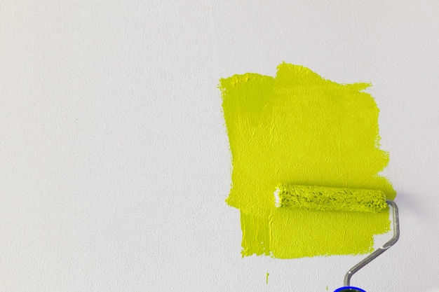 Qualcuno dipinge un muro bianco con un colore giallo brillante