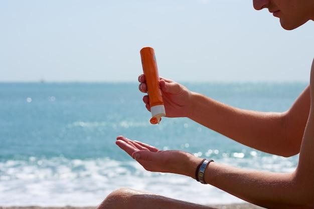 Qualcuno che si mette la crema solare tra le mani in spiaggia