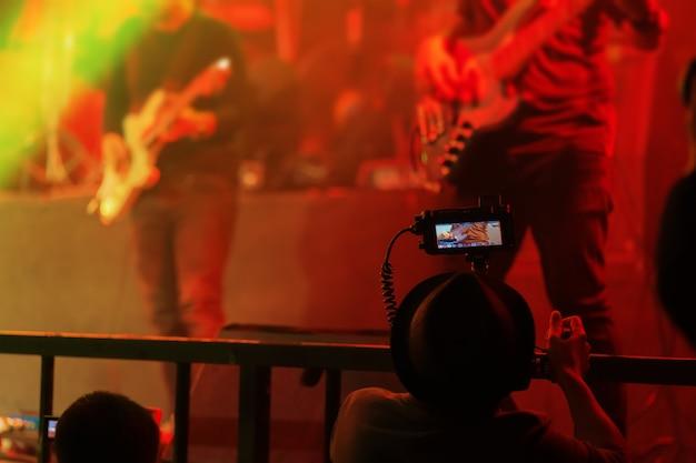 La fotocamera dslr di qualcuno con la ripresa di un concerto con l'immagine live view su uno schermo.