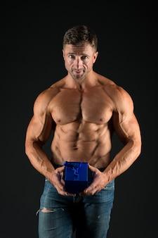 Qualcosa di speciale. sportivo che fa regalo. torso muscoloso macho tenere confezione regalo. petto muscoloso macho atletico sexy. l'uomo atleta ha un regalo per te. il giorno di san valentino concetto. regalo di festa del culturista.