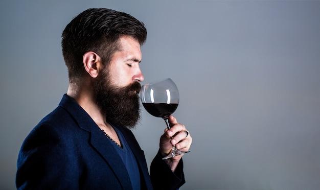 Sommelier, degustatore con bicchiere di vino rosso, azienda vinicola, enologo maschio.