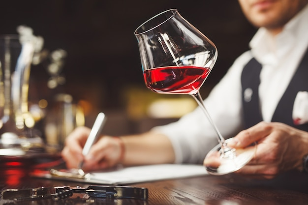 Il sommelier compila il modulo che descrive la qualità del vino rosso costoso in un bicchiere di vino seduto al tavolo in un ristorante di lusso primo piano