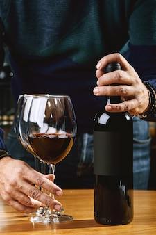 Le mani del sommelier nella cornice offrono e versano il vino in un bicchiere