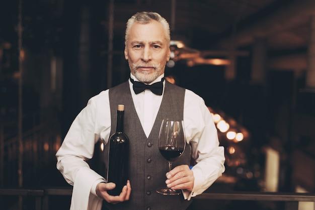 Il sommelier sta tenendo il vino in vetro e bottiglia