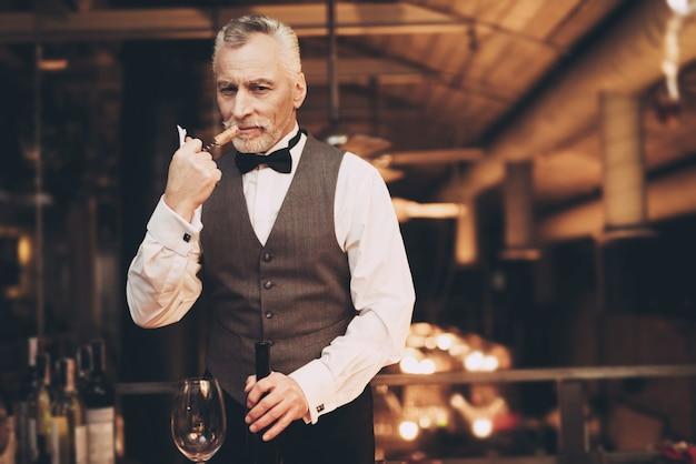 Sommelier sta sniffando cork of wine in restaurant