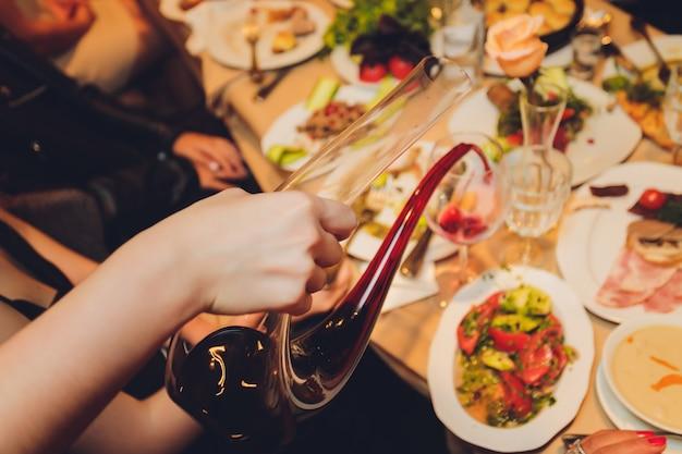 Sommelier che versa il vino nel bicchiere dalla ciotola di miscelazione alla cena di lusso.