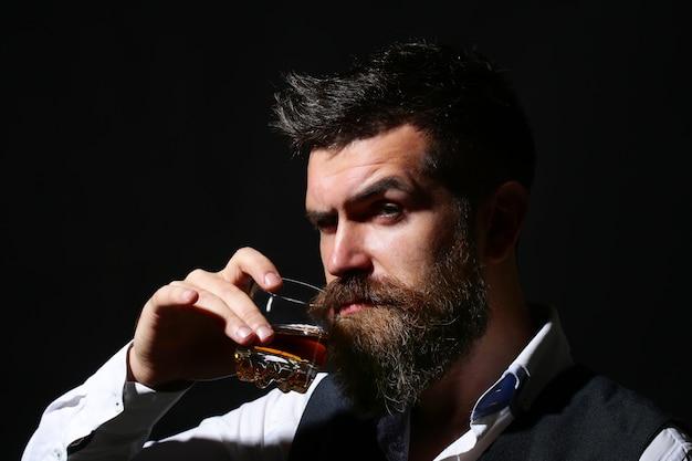 Il sommelier assaggia una bevanda costosa. barbuto uomo d'affari in abito elegante con bicchiere di brandy. concetto di degustazione e degustazione.