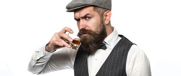Il sommelier assaggia una bevanda costosa. uomo bello ben vestito in giacca con un bicchiere di bevanda. uomo barbuto che indossa tuta e beve whisky, brandy, cognac. barbuto sta tenendo in mano un bicchiere di whisky.