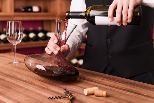 Sommelier al lavoro. sommelier maschio fiducioso che versa vino nel decanter mentre si trova vicino allo scaffale del vino