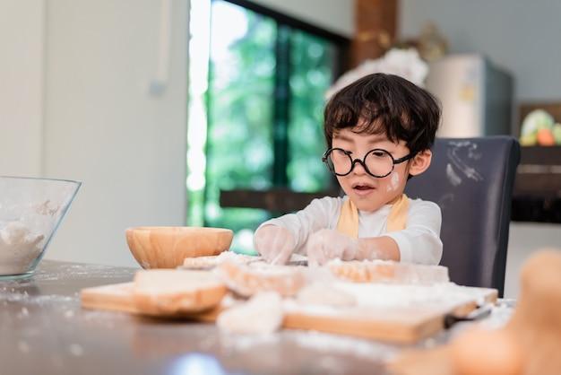Figlio che cucina cibo. preparare un ingrediente con farina e pane. stile di vita quotidiano per bambini a casa. famiglia asiatica in cucina.