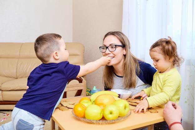 Il figlio dà da mangiare a sua madre mamma mela nella stanza a tavola