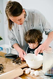 Il figlio aiuta la madre a cucinare in cucina