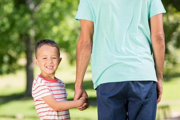 Figlio che tiene le mani di suo padre nel parco