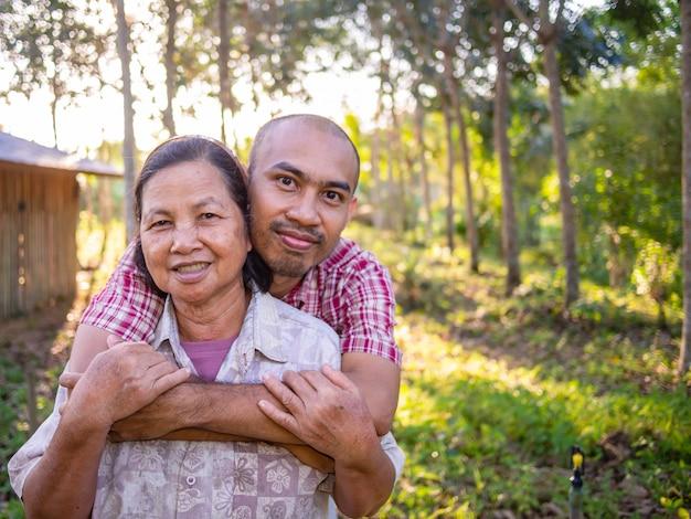 Figlio che abbraccia madre nella piantagione di gomma.