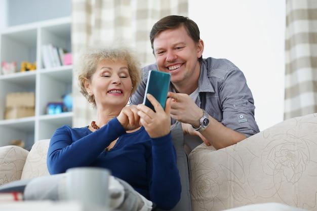 Figlio e madre che sorridono e guardano lo schermo del telefono