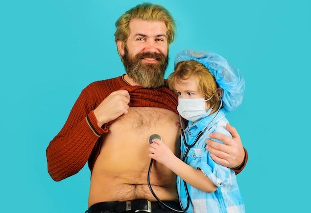 Il figlio gioca al dottore con il padre, il dottore bambino gioca con il padre, la medicina e la salute.
