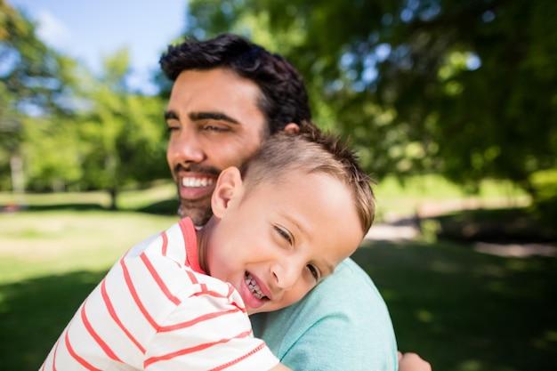 Figlio che sorride mentre abbraccia suo padre nel parco