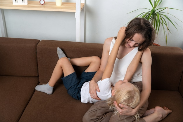 Figlio con madre chat e abbraccio. mamma e figlio giocano a casa.