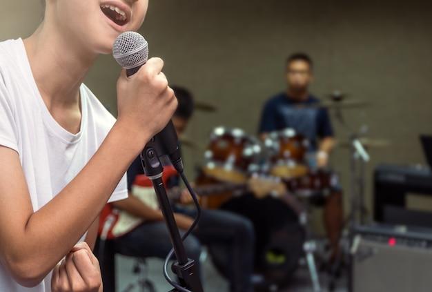 Mano di songer che tiene il microfono e canta sul musicista