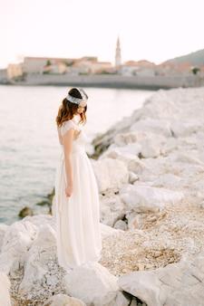 Una sposa sofisticata si trova su una pittoresca costa rocciosa vicino al centro storico di budva