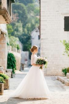 Una sposa sofisticata sta con un bouquet da sposa tra le mani vicino a una casa di mattoni bianchi nel