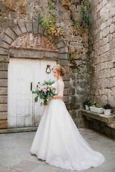 Una sposa sofisticata sta con un bouquet da sposa in mano vicino a una porta di legno bianca nel
