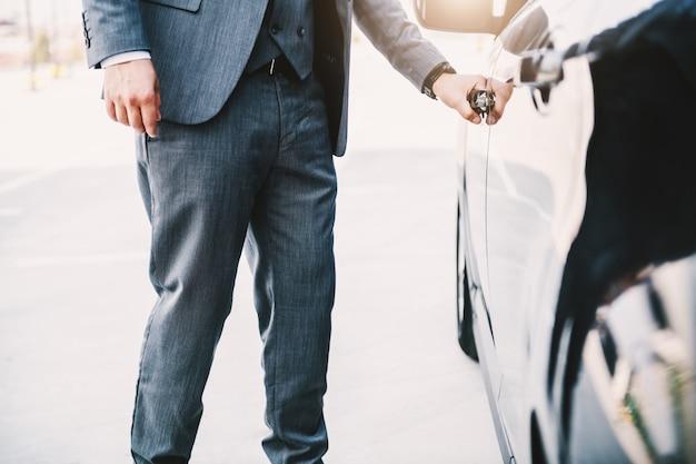 Uomo d'affari ricco sofisticato che apre la sua macchina.