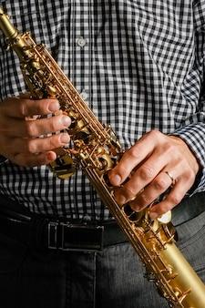 Sassofono soprano nelle mani su uno sfondo nero