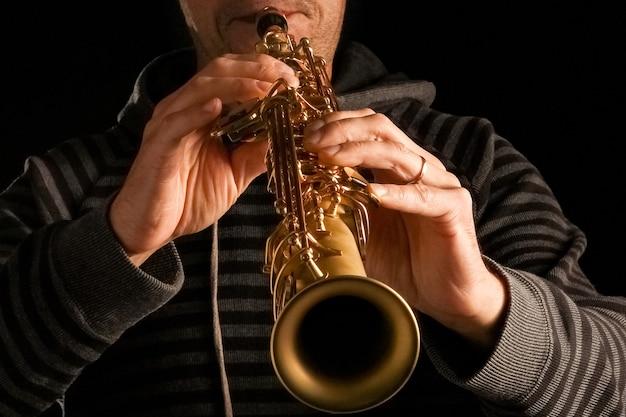 Sassofono soprano nelle mani di un ragazzo su una superficie nera