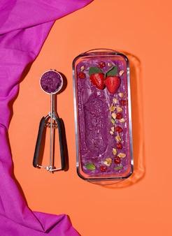 Sorbetto ai mirtilli su uno spazio arancione in una ciotola di vetro. vista dall'alto