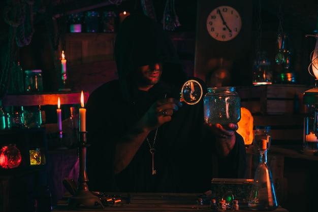 L'alchimista stregone in abiti scuri è impegnato nella produzione di pozioni in un laboratorio artigianale con una luce al neon colorata