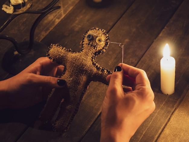 Una maga trafigge una bambola voodoo con uno spillo, provocando danni o danni a una persona, primo piano.
