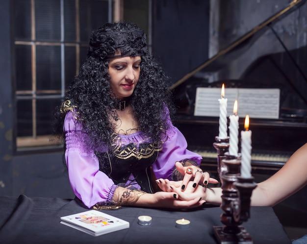 Incantatrice che legge la mano di qualcuno