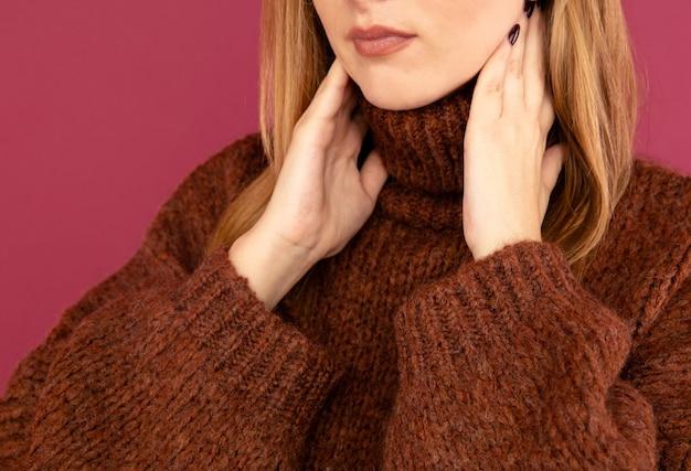 Concetto di mal di gola. vista del primo piano della donna in maglione che tiene il suo collo nel dolore.