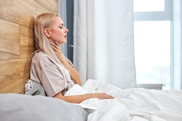 Mal di gola nella stagione del coronavirus influenzale. donna che si tocca il collo e sente dolore mentre è seduta in camera da letto a casa da sola, che soffre di sintomi covid-19.