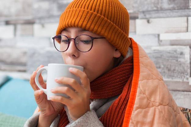 Una ragazza con mal di gola sta bevendo tè caldo.