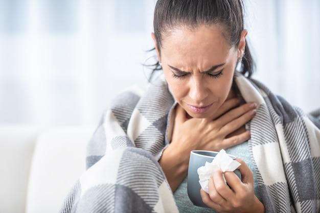 Mal di gola di una donna con un raffreddore a casa durante una stagione influenzale.