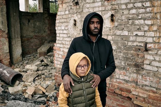 Giovane uomo di colore addolorato in felpa con cappuccio che abbraccia la piccola figlia intorno alle spalle mentre sta in piedi con...