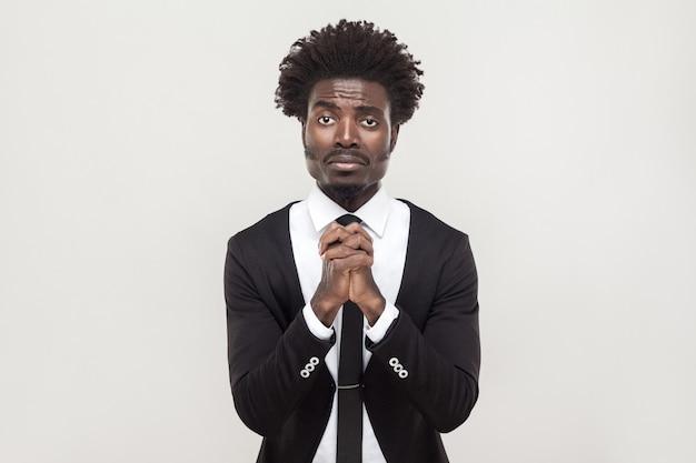 Siamo spiacenti, concetto di speranza. uomo d'affari africano che guarda l'obbiettivo e si scusa. foto in studio, sfondo grigio
